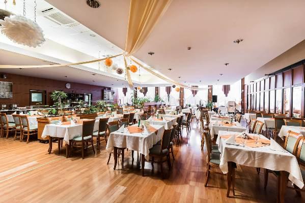 Megterített éttermi asztalok, feldíszített Barátság terem