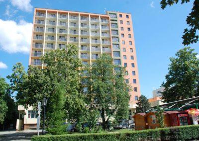Hotel épülete előtérben zöld fákkal